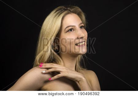 Portrait Of A Smiling Girl On A Dark Background.