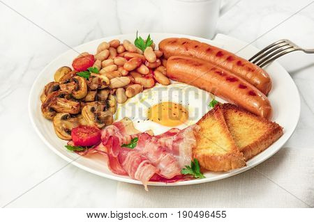 A photo of a plate of English breakfast on a white marble texture, with a sunny side up egg, sausages, bacon, toasts, grilled mushrooms and tomatoes, a cup of coffee in the background, and copy space