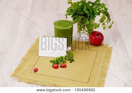 Green cocktail of parsley and greens in a glass on a table with a napkin made from canvas, detoxification and diet food for breakfast. Detox