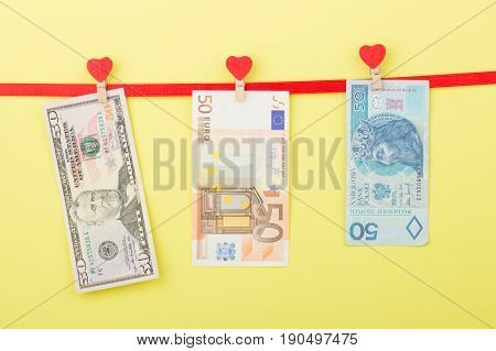 Fifty Dollars, Zloty And Euro Hangs On The Clothespins, Yellow Background
