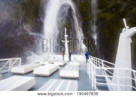 MILFORD SOUND NEW ZEALAND - AUGUST 302015 : tourist taking a photograph while milford sound cruise approach heading of ship to high waterfalls in fiord and national park most popular traveling destination in south island new zealand