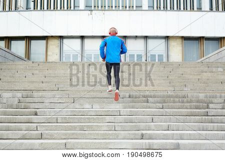 Young man running upstairs in urban environment
