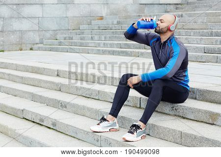 Thirsty athlete drinking fresh water while sitting on staircase