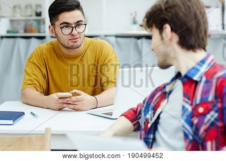 Attentive student listening to his groupmate during conversation