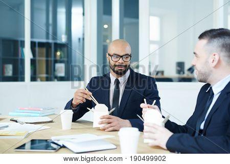 Small group of businessmen having lunch break in office