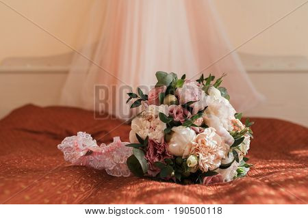Beautiful lush wedding bouquet of pink flowers and bride's garter on bed with wedding dress on background in bride's bedroom