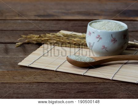 Japanese rice in wood spoon on bamboo sushi mat. Little lovely bowl filled with Japanese rice on rustic wood. Natural tone style of Japanese rice of background and wallpaper with copy space. Japanese rice in lovely bowl and wood spoon.