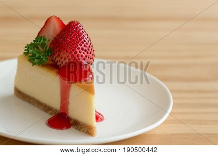 Homemade New York cheesecake on white plate decorated by strawberry, parsley and strawberry sauce. Moist and smooth classic baked cheesecake. Copy space background of delicious New York cheesecake. Triangle slice of strawberry cheesecake.