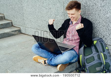 Happy Young Man With Laptop Computer. I Did It! Handsome  Man Looking At Computer Monitor On His Kne