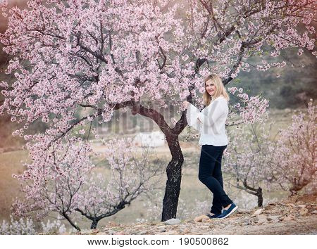 Beautiful young woman in a beautiful flowering gardens