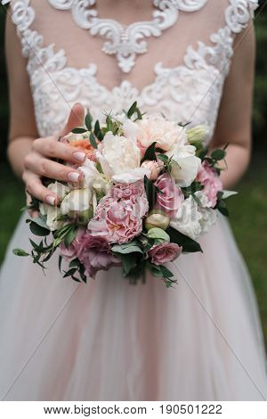 Lush Wedding Bouquet Of White And Pink Peonies, Roses And Greenery In The Bride's Hands. Bride With