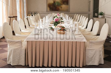 Chairs With White Cloth And Table For Guests Served For Wedding Banquet With Flowers. Peony On Dinne