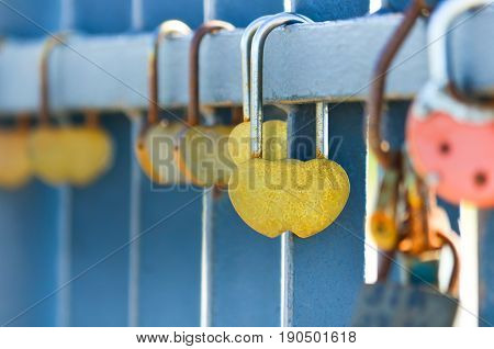 Many padlocks hanging on the metal fence. Closeup