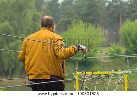 Close up man crossing the river on the rope bridge with belay