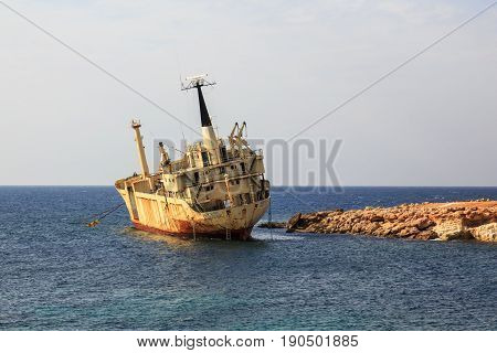 Seascape: boat EDRO III shipwrecked near the rocky shore at the sunset. Mediterranean near Paphos. Cyprus