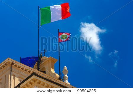 Beautiful large waving the flag of Italy and Italian Presidential pennant over Quirinal Palace against the blue sky, Rome, Italy.