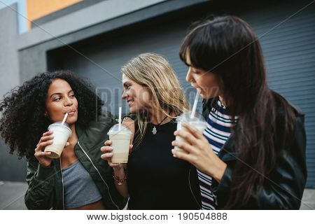 Group Of Female Friends Having Ice Coffee Outdoors