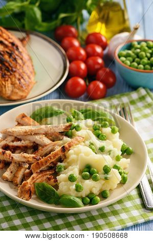 Grilled turkey fillet with mashed potatoes and green peas.