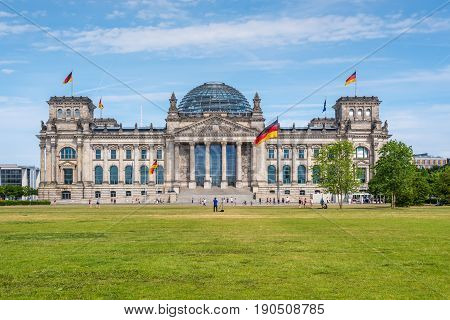 Berlin Germany - May 28 2017: Reichstag building German Parliament people enjoying a spring day. The dedication Dem deutschen Volke meaning To the German people can be seen on the frieze.