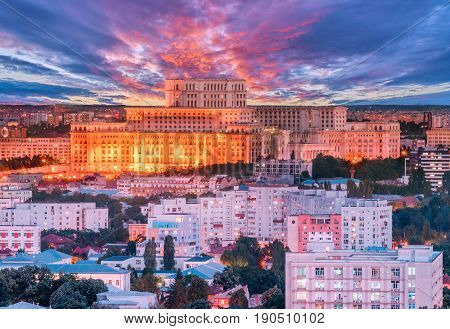 Aerial view of the Parliament building in Bucharest, Romania with dramatic red sunset.