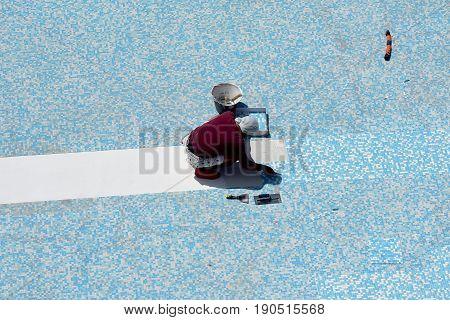 Worker kneeling at the floor  renovates a pool tub