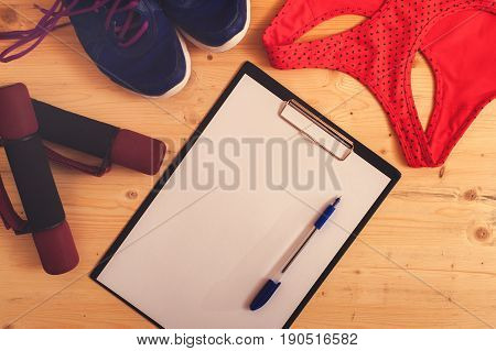 Sports and fitness accessories: dumbbells, sneakers, sports bra and blank clipboard with pen. Healthy lifestyle concept.