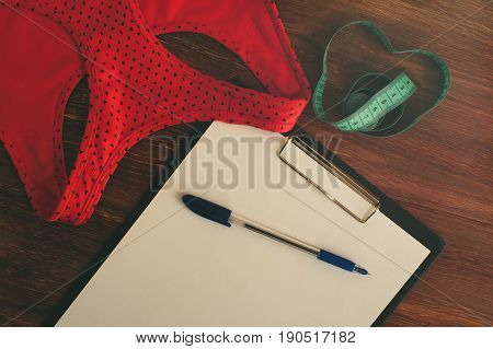 Sports bra, measuring tape and blank clipboard with pen. Sports and fitness equipment. Weight loss and healthy lifestyle concept.