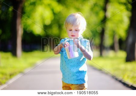 Concentrated Little Kid Boy Drawing With Colored Chalk On Asphalt
