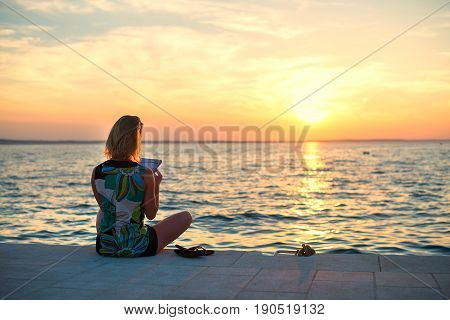 beautiful young woman sitting on a pier and reading book