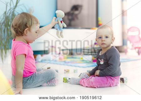 Two cute girls playing at home at the teacher. Big sister teaching her sibling.