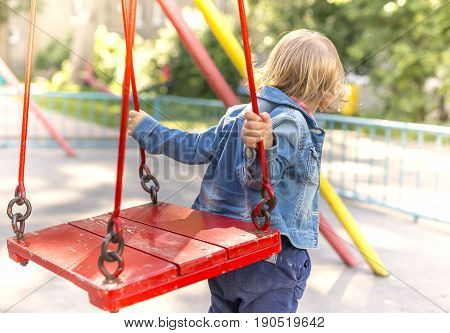 A two-year-old girl jumps or jumps on a swing in the park.