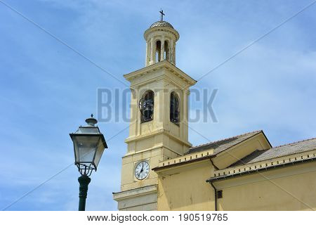 Street lamp in the foreground and in the background the bell tower of the church