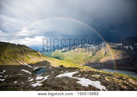 rainbow in the mountains with mountain lake and cloudy sky