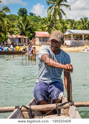 Ambatozavavy Nosy Be Madagascar - December 19 2015: Boatman on his traditional wood pirogue with outrigger in the fishing Ambatozavavy village on the Nosy Be island Madagascar.