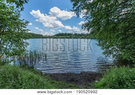 Lake Side On The Shore With Trees And Ripples Waves On The Water. Maars Vulcan In Germany