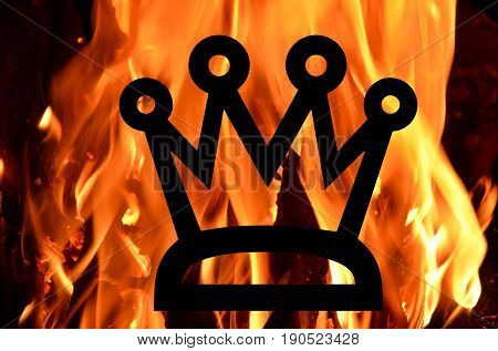 Black crown against the background of tongues of burning flames.