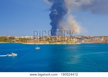 Malta, Valletta - May 22, 2017: A huge pillar of black smoke over bay of the city Valletta due to a fire at Sant Antnin recycling plant.