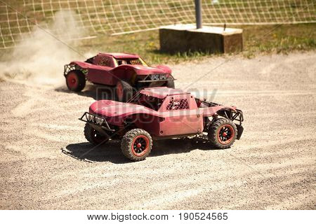 Two small radio controlled model cars racing in the dust. Miniature remote controlled buggy racing hobby