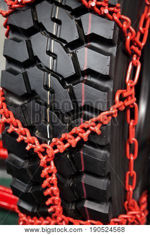 New clean studded tire chains close-up. Black wheel wrapped in red snow chains