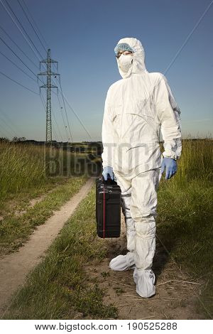 Criminologist technician dressing disposable overall and protective equipment
