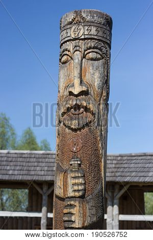 ancient pagan temple with wooden idol and house from tree bars in ethnic style in the medieval settlement