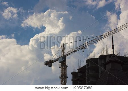 high construction crane build unfinished city housing against the background of the blue sky and clouds. horizontal shot