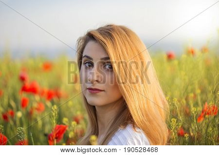 Portrait of blonde woman in white dress standing on field of poppies