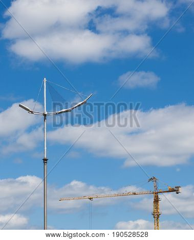 high construction crane and city light stand pole against the background of the blue sky and clouds