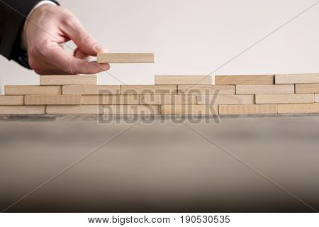 Male hand completing building wall of wooden bricks on table copy space.