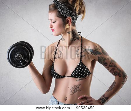Tattooed woman with fit body doing weight-lifting