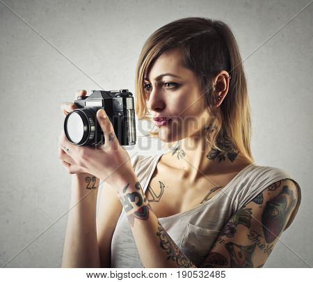 Tattooed girl using a vintage camera