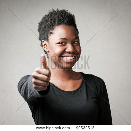 Happy black woman smiling with thumb up