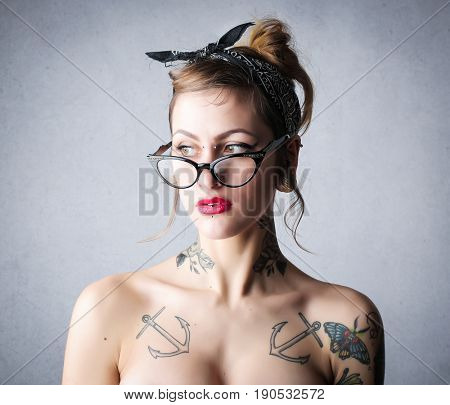 Tattooed girl wearing glasses and colorful lipstick