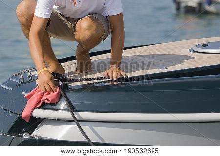 Barefoot sailor cleans the boat with a pink cloth